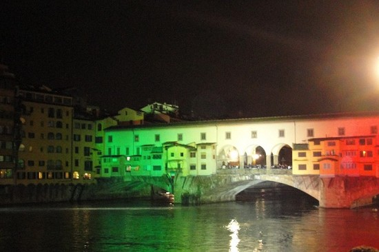 the old bridge by night illuminated by the colors of the Italian flag